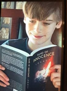 11-year-old boy reading Band of Innocence - Legacy book