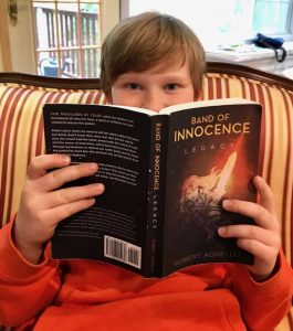 Pre-teen boy reading Band of Innocence Legacy book