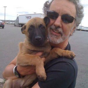 Robert Agnello holding Jack the puppy at airport