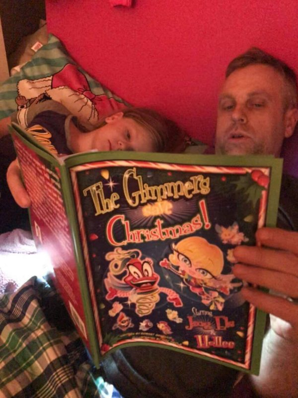 Dad and son on couch reading The Glimmers Save Christmas
