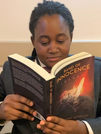 Young African-American girl reading Band of Innocence